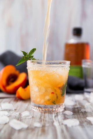 Bebida de uísque, pêssego e hortelã
